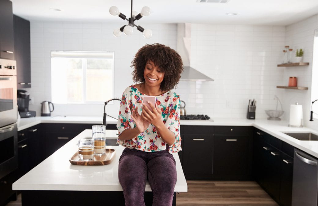 woman sitting atop a counter in a stylish kitchen