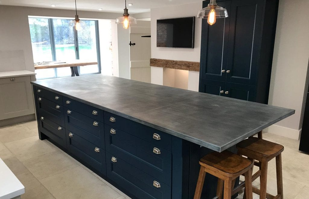 Simple deep blue kitchen island with zinc worktop by Ashford Kitchens and Interiors Ltd.